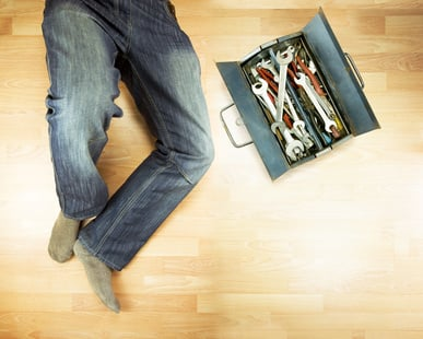 A man's legs in jeans next to a toolbox on a kitchen floor, implying that he is working on the sink.